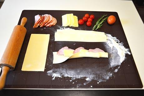 В центр теста поочередно выкладываем колбасу и сыр