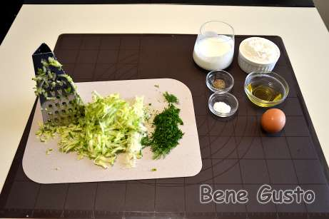 Кабачок натираємо на крупній тертці, цибулю та зелень дрібно рубаємо ножем