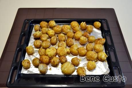 Затем выкладываем картофель на противень в один слой и слегка придавливаем толкушкой, чтобы она только лопнула