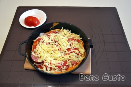 Запеченное тесто смазываем кетчупом и выкладываем начинку в произвольном порядке: лук, колбаса, помидоры и посыпаем сыром.
