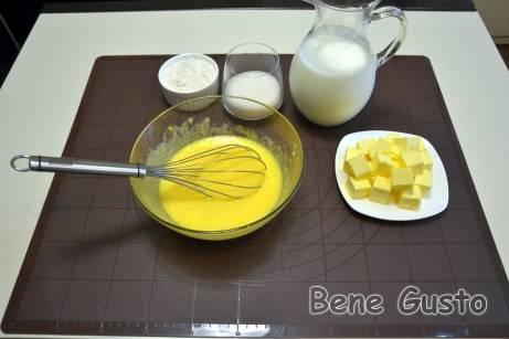 В миску закладываем 5 желтков и 1 целое яйцо, высыпаем сахарный песок и ванильный сахар. Хорошо перемешиваем.
