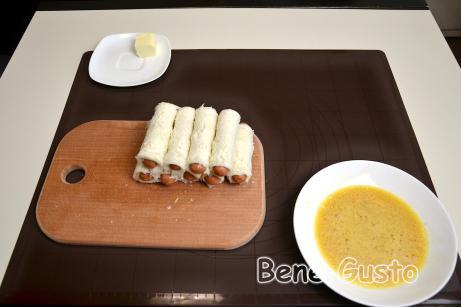 Ломтик хлеба смазываем плавленым сыром, кладем сосиску и сворачиваем трубочкой